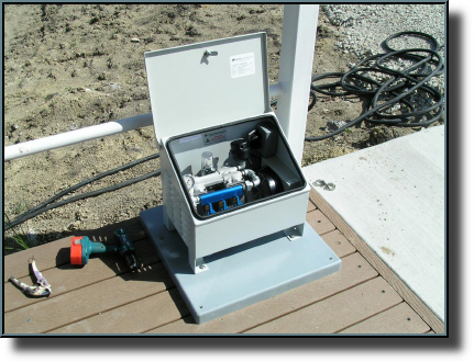 Electric aeration compressor and control box. Weighted air hose in background.